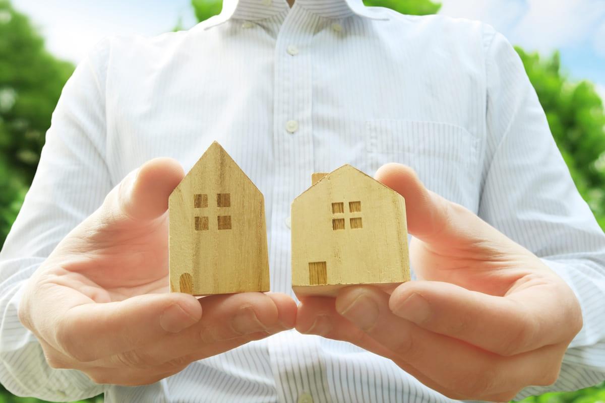 家の模型を両手に持つ